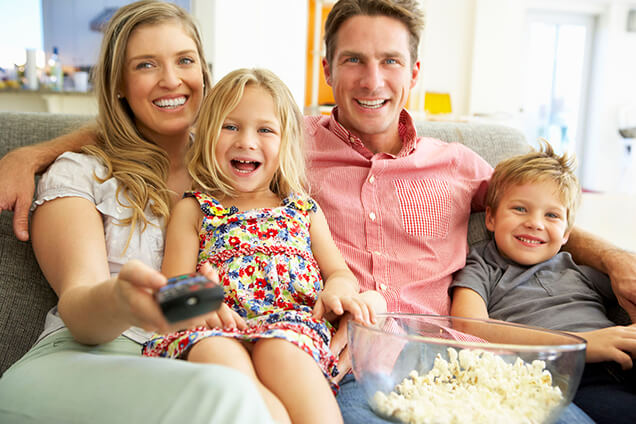 family enjoying indoor air quality while on sofa watching tv and eating popcorn