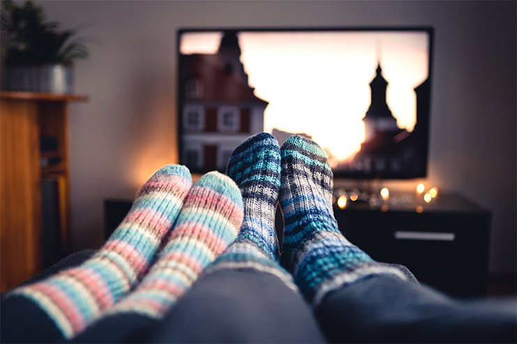 couple enjoying their cozy warm home in front of the television
